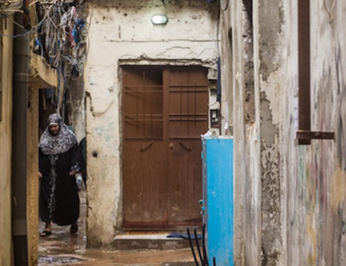 An elderly Palestinian woman walking down an alley. Source: Jason Lemon