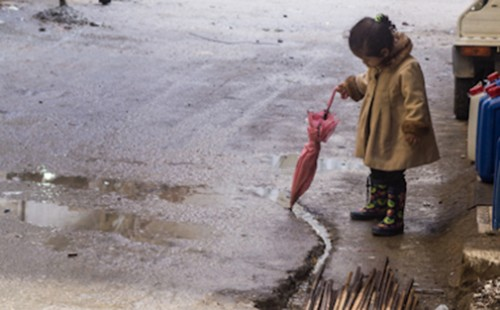 A young Palestinian girl traces a crack with her umbrella. Source: Jason Lemon